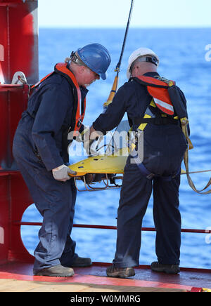 Phoenix International personnel deploy a 'towed pinger locator' off the deck of Australian Defense Vessel Ocean Shield in the search for the flight data recorder and cockpit voice recorder of a Malaysia Airlines jetliner missing in the Indian Ocean, about 1,000 miles off the coast of Perth, Australia.  The U.S. Navy 'towed pinger locator' connected to the Ocean Shield picked up signals consistent with that of the missing jetliner it was announced today April 7, 2014.   UPI/Kelly Hunt/Australian Defense Force - Stock Photo