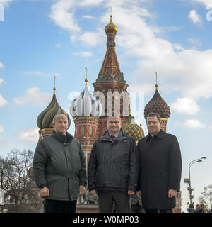 Expedition 47 crew members: NASA astronaut Jeff Williams, left, Russian cosmonauts Alexei Ovchinin, center, and Oleg Skripochka of Roscosmos, pose for a photograph in front of Saint Basil's Cathedral in Red Square shortly after having laid roses at the site where Russian space icons are interred as part of traditional pre-launch ceremonies on Friday, February 26, 2016 in Moscow, Russia.   NASA Photo by Bill Ingalls/UPI - Stock Photo