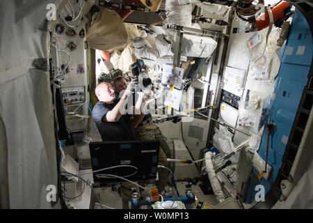 NASA astronaut Scott Kelly (left) and ESA (European Space Agency) astronaut Timothy Peake (right) review images during a January 10, 2016 procedure to replace a fan pump separator inside one of the U.S. spacesuits aboard the International Space Station. The activity took place inside the Quest airlock where all U.S. based spacewalks begin and end. NASA/UPI - Stock Photo