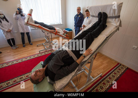 Expedition 43 crew members Gennady Padalka, background, and Mikhail Kornienko of the Russian Federal Space Agency (Roscosmos) take part the tilt table training during media day, on March 21, 2015, Baikonur, Kazakhstan. ..Part of NASA's Human Research Program, the One-Year Mission on the International Space Station is a joint effort between the U.S. space agency, the Russian Federal Space Agency (Roscosmos) and their international partners. The mission is part of a scientific research project studying long term spaceflight and the effects it has on the human body...NASA astronaut Scott Kelly an - Stock Photo