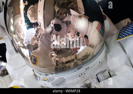 NASA astronaut Scott Kelly snaps a quick space selfie during his first ever spacewalk on October 28, 2015. Kelly and fellow NASA astronaut Kjell Lindgren worked outside for seven hours and 16 minutes on a series of tasks to service and upgrade the International Space Station. They wrapped a dark matter detection experiment in a thermal blanket, lubricated the tip of the Canadarm2 robotic arm and then routed power and data cables for a future docking port. ..Part of NASA's Human Research Program, the One-Year Mission on the International Space Station is a joint effort between the U.S. space ag - Stock Photo