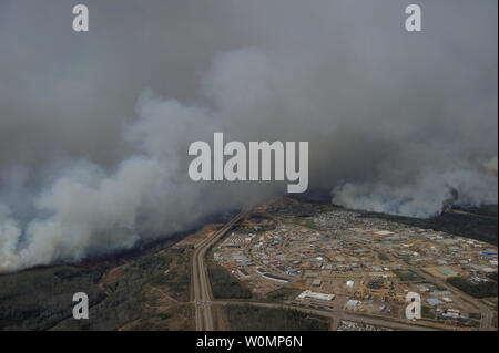 Aerial view of the wildfires in the Fort McMurray area from a CH-146 Griffon on May 4, 2016. The Canadian Armed Forces have deployed air assets to the area to support the Province of Alberta's emergency response efforts. At the time this image was taken, a mandatory evacuation had been placed on all of Fort McMurray - the largest evacuation on record in Canada. The fire had burned through nearly 77 square kilometers, razing neighborhoods across the city. Photo by MCpl VanPutten/Canadian Armed Forces/UPI - Stock Photo