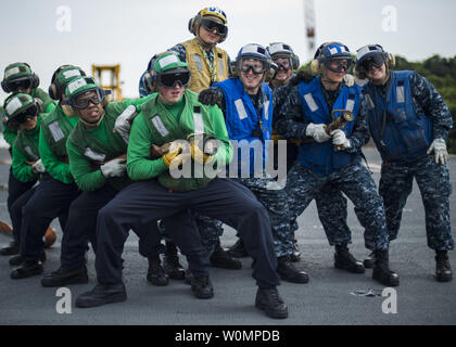Air department Sailors pose for a photo on the flight deck of the U.S. Navy's only forward-deployed aircraft carrier USS Ronald Reagan (CVN 76) after completing a fire fighting drill in Yokosuka, Japan, on May 16, 2016. Ronald Reagan provides a combat-ready force which protects and defends the collective maritime interests of the U.S. and its allies and partners in the Indo-Asia-Pacific region. Photo by Mass Communication Specialist Seaman Jamaal Liddell/U.S. Navy/UPI - Stock Photo