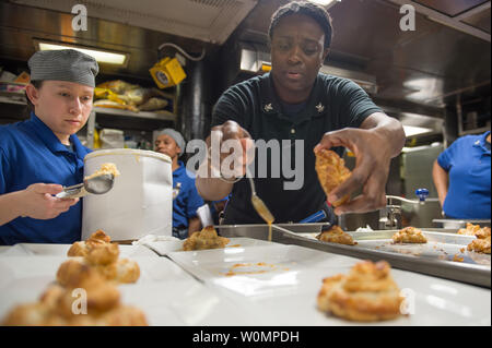 Culinary Specialist 2nd Class Crystal T. Holmes (right) and Seaman Asucena C. Martinez (left), prepares pastries for a monthly birthday meal for the crew aboard the forward-deployed Arleigh Burke-class guided-missile destroyer USS Barry (DDG 52) transiting the Luzon Strait on May 26, 2016. Barry is on patrol in the U.S. 7th Fleet area of operations in support of security and stability in the Indo-Asia-Pacific. Photo by Mass Communication Specialist 2nd Class Kevin V. Cunningham/U.S. Navy/UPI - Stock Photo