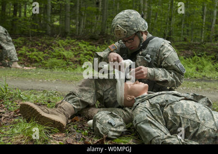 U.S. Army Pfc. Daniel Aguilar, assigned to Bravo Company, 3rd Battalion, 172nd Infantry Regiment, 86th Infantry Brigade Combat Team (Mountain), Vermont National Guard, applies bandages to a training dummy during a medical lane at Camp Ethan Allen Training Site, Jericho, Vt., June 14, 2016. Soldiers conduct lanes during their annual training for evaluation so they know what they need more practice on. Photo by Avery Cunningham/U.S. Army National Guard/UPI - Stock Photo