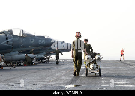 Marines prepare to load ordnance onto an AV-8B Harrier II, assigned to 13th Marine Expeditionary Unit (MEU), on the flight deck of amphibious assault ship USS Boxer (LHD 4) in preparation for missions in support of Operation Inherent Resolve on June 16, 2016. Boxer is the flagship for the Boxer Amphibious Ready Group and, with the embarked 13th Marine Expeditionary Unit, is deployed in support of maritime security operations and theater security cooperation efforts in the U.S. 5th Fleet area of operations. Photo by Brian Caracci/U.S. Navy/UPI - Stock Photo