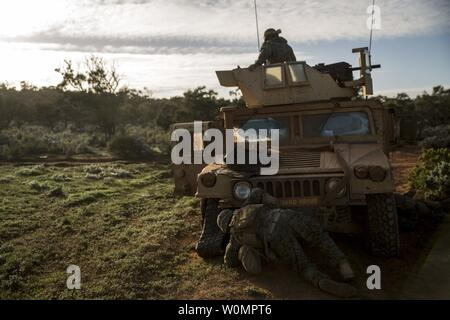 U.S. Marines with Weapons Company, 1st Battalion, 1st Marine Regiment, Marine Rotational Force - Darwin, stop to fix a flat tire at Cultana Training Area, South Australia, Australia, July 1, 2016. The difficult terrain challenges Australian, New Zealand, and U.S. forces during Exercise Hamel, a trilateral training exercise to enhance cooperation, trust, and friendship. Photo by Mandaline Hatch/U.S. Marine Corps/UPI - Stock Photo