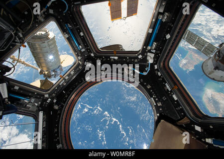 Orbital ATK's Cygnus cargo craft (left) is seen from the Cupola module windows aboard the International Space Station on October 23, 2016. The main robotic work station for controlling the Canadarm2 robotic arm is located inside the Cupola and was used to capture Cygnus upon its arrival. The Expedition 49 crew will unload approximately 5,000 pounds of science investigations, food and supplies from the newly arrived spacecraft. NASA/UPI - Stock Photo