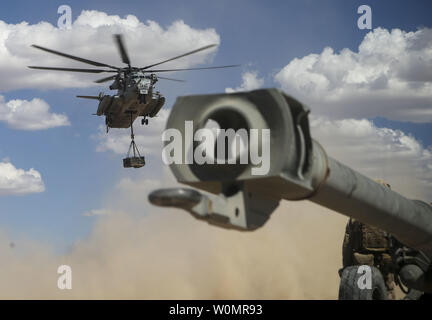 A U.S. Marine Corps CH-53E Super Stallion assigned to Marine Aviation Weapons and Tactics Squadron One (MAWTS-1) prepares to land with 155mm M777 Howitzer ammunition during a CH-53 day battle drill exercise at Fire Base Burt, Calif., on October 1, 2016. The CH-53 battle drill is part of Weapons and Tactics Instructor (WTI) 1-17, a seven-week training event hosted by MAWTS-1 cadre. MAWTS-1 provides standardized tactical training and certification of unit instructor qualifications to support Marine Aviation Training and Readiness and assists in developing and employing aviation weapons and tacti - Stock Photo