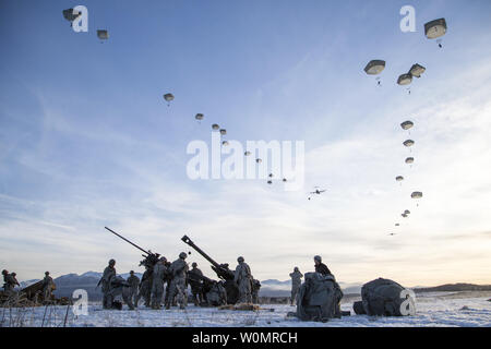Paratroopers assigned to A Battery, 2nd Battalion, 377th Parachute Field Artillery Regiment, 4th Infantry Brigade Combat Team (Airborne), 25th Infantry Division, U.S. Army Alaska, descend over Malemute drop zone while conducting airborne and live fire training at Joint Base Elmendorf-Richardson, Alaska, November 22, 2016. Photo by Alejandro Pena/U.S. Air Force/UPI - Stock Photo