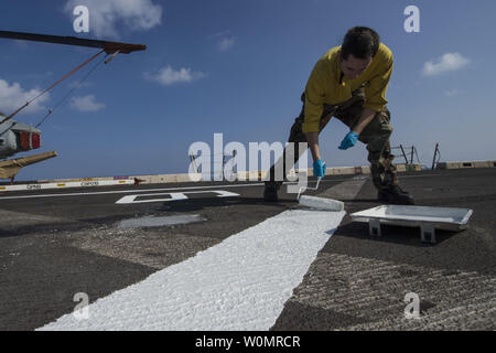 Seaman Brad McNamee paints the flight deck aboard the amphibious transport dock ship USS San Antonio (LPD 17) on November 23, 2016. San Antonio is deployed with the Wasp Amphibious Ready Group to support maritime security operations and theater security cooperation efforts in the U.S. 6th Fleet area of operation. Photo by Petty Officer 2nd Class Adam Austin/U.S. Navy/UPI - Stock Photo