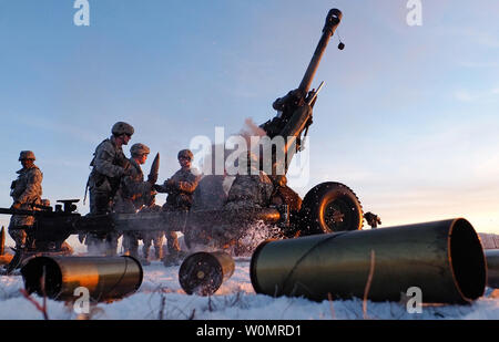 Paratroopers assigned to Alpha Battery, 2nd Battalion, 377th Parachute Field Artillery Regiment, 4th Infantry Brigade Combat Team (Airborne), 25th Infantry Division, U.S. Army Alaska, reload a M119A2 105mm howitzer during a live fire on Malemute drop zone at Joint Base Elmendorf-Richardson, Alaska, November 22, 2016. USARAK is home to the ArmyÕs only Pacific airborne brigade combat team, and maintains the only airborne rapid-response capacity within the Pacific Command Area of Responsibility. Photo by Justin Connaher/U.S. Air Force/UPI - Stock Photo