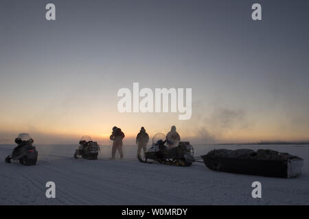 A team including U.S. Marine Corps 1st Sgt. Joshua Guffey, left, Capt. Michael Sickels, right, assigned to Detachment Delta, 4th Law Enforcement Battalion, and local resident Robert Kirk, center, pause to adjust their gear while traveling via snow machine across the Northwest Arctic Borough in Alaska, December 4, 2016. Guffey, Sickels and Kirk, traveled across the Northwest Arctic Borough to deliver holiday gifts for Alaskan children while participating in Toys for Tots. Toys for Tots is supported by the United States Marine Corps Reserve with a goal of delivering, through a new toy during the - Stock Photo