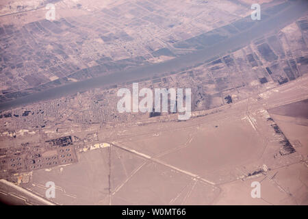 Towns along the Iran, Iraq border along the Shatt al-arab river with oil spills in foreground. - Stock Photo