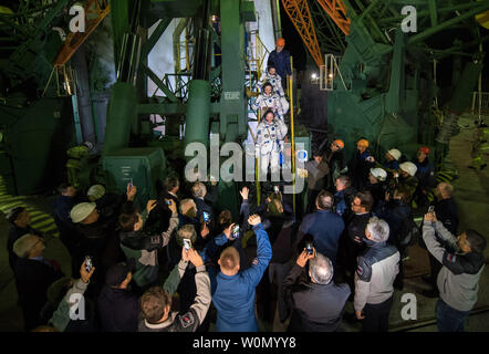 Expedition 55 flight engineer Drew Feustel of NASA, top, flight engineer Ricky Arnold of NASA, middle, and Soyuz Commander Oleg Artemyev of Roscosmos, bottom, wave farewell prior to boarding the Soyuz MS-08 spacecraft for launch, on March 21, 2018, at the Baikonur Cosmodrome in Kazakhstan. Feustel, Arnold, and Artemyev will spend the next five months living and working aboard the International Space Station. NASA Photo by Joel Kowsky/UPI - Stock Photo