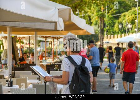 GARDA, ITALY - SEPTEMBER 2018: Two people studying the menu of a lakeside restaurant in Garda on Lake Garda. - Stock Photo