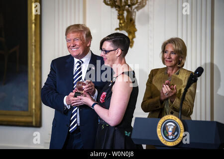 U.S. President Donald Trump presents the National Teacher of the Year award to Mandy Manning, as Betsy DeVos, U.S. secretary of education, looks on, during the National Teacher of the Year reception, in the East Room of the White House, in Washington, D.C., on May 2, 2018. Photo by Al Drago/UPI - Stock Photo