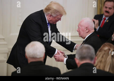 U.S. President Donald Trump shakes hands with former Commandant of the Marine Corps retired Gen. Alfred Gray while commemorating the 35th anniversary of attack on the Beirut Barracks in the East Room of the White House October 25, 2018 in Washington, DC. On October 23, 1983 two truck bombs struck the buildings housing Multinational Force in Lebanon (MNF) peacekeepers, killing 241 U.S. and 58 French peacekeepers and 6 civilians.     Photo by Chip Somodevilla/UPI - Stock Photo