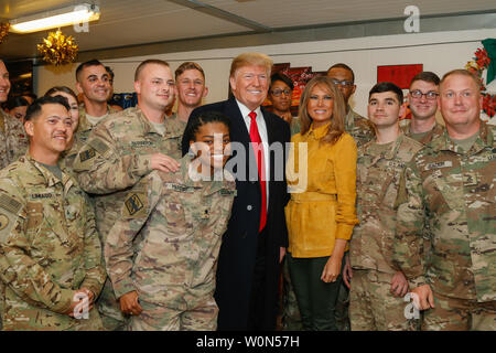 U.S. President Donald J. Trump and first lady Melania Trump pose for a photo with service members assigned to Combined Joint Task Force - Operation Inherent Resolve (CJTF-OIR) during a troop visit to Al Asad Air Base, Iraq, December 26, 2018. CJTF-OIR works by, with, and through partner forces to defeat ISIS. Photo by 1st Lt. Leland White/U.S. Army National Guard/UPI - Stock Photo
