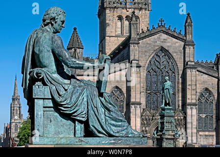The statue of David Hume by sculptor Alexander Stoddart  on the Royal Mile in Edinburgh with St Giles Cathedral in the background. - Stock Photo