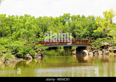 Delray Beach, Florida, Morikami Japanese Botanical Garden, beautiful bridge, waterfall and walkway along the lake among a lush foliage backdrop