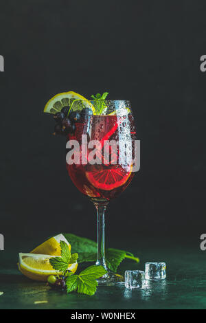 Cold red cocktail with blackcurrant, lemon, mint and ice in tall glass on black background. Summer drinks and alcoholic cocktails. Alcoholic cocktail - Stock Photo