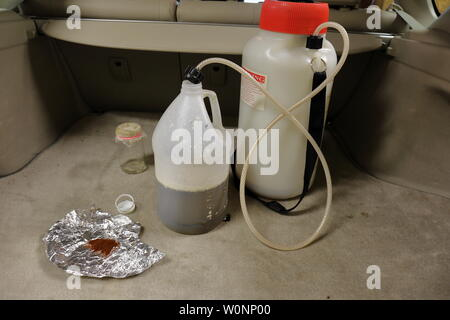 Supplies and chemicals used to manufacture methamphetamine in the back of a vehicle - Stock Photo