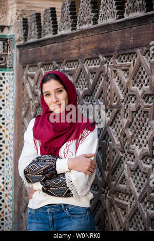 Arms crossed muslim woman in traditional clothing with red hijab and jeans in front of traditional arabesque decorated wall - Stock Photo