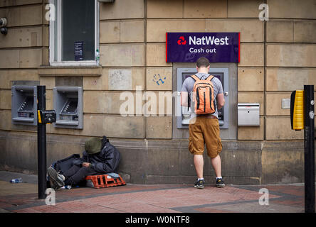 Manchester city centre, Natwest cash machine ATM with person begging next to the whole in the wall dispenser - Stock Photo