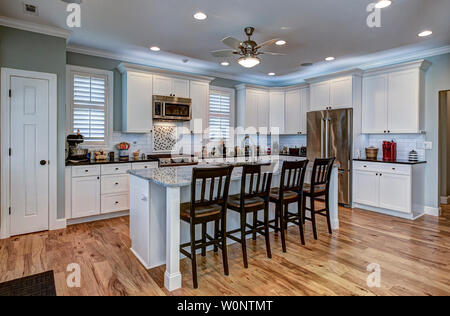 Expensive kitchen with white cabinets and hardwood flooring and granite counters. - Stock Photo