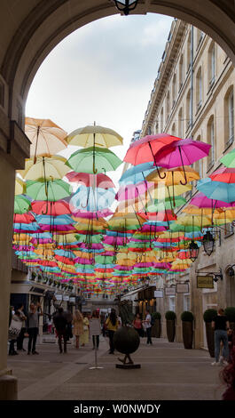 The Umbrella Sky Project by Patricia Cunha deligts visitors to Le Village Royal in Paris France also shown is a sculpture by Dirk De Kayzer - Stock Photo
