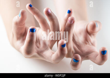 A mother paints her young girl's hands with blue and pink nailpolish, viewed against an isolated white background - Stock Photo