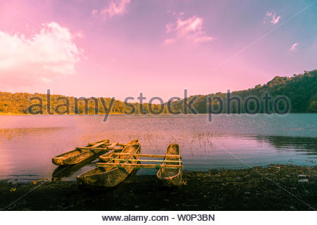 Fishing boats at sunset on the shore of Lake Tamblingan in Bali, Indonesia - Stock Photo
