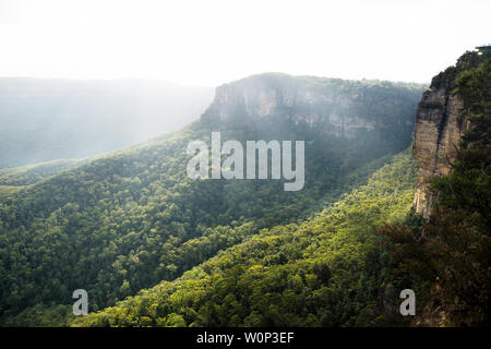 Sunrays over the Blue mountains at three sisters rock formation during sunset, Katoomba, New South Wales, Australia - Stock Photo