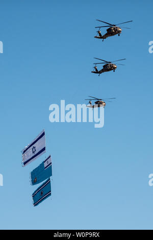 Hazerim Air Base, Israel. 27th June, 2019. IAF Black Hawk helicopters drag flags at an air show taking place at a graduation ceremony honoring newly certified Israel Air Force pilots and navigators following their successful completion of one of the most competitive and rigorous training processes in the IDF at Hazerim Air Base in the Negev Desert. Credit: Nir Alon/Alamy Live News. - Stock Photo