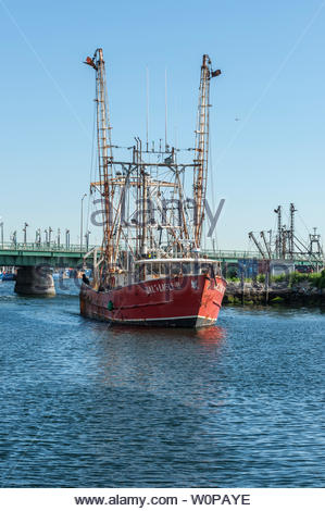 New Bedford, Massachusetts, USA - June 8, 2019: Commercial fishing vessel Bald Eagle II easing away from ice house dock in New Bedford - Stock Photo
