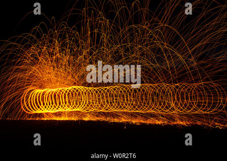 Firescape night photography. Having fun creating art with wire wool and fire at night. - Stock Photo