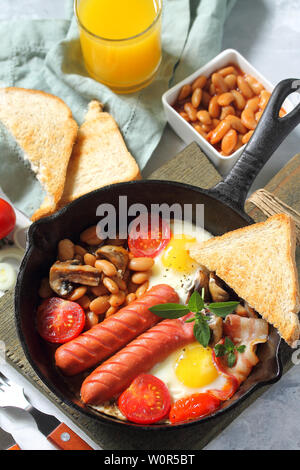 Breakfast in English scrambled eggs with bacon, beans, mushrooms, sausages, tomatoes and juice on light stone table. - Stock Photo
