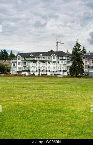 New residential low-rise building with huge green lawn in front on cloudy day - Stock Photo