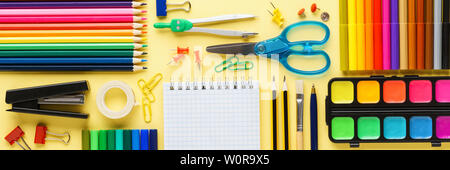 Set of various colorful school stationery and supplies on yellow background. Geometrically aligned flat lay. Banner. - Stock Photo