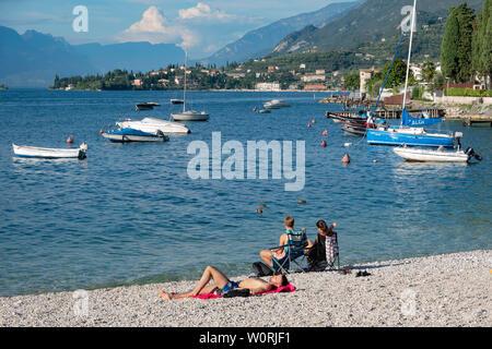 Cassone, Garda Lake, Italy,. Tourists relaxing and sunbathing on the beach of Lake Garda near Cassone - Stock Photo