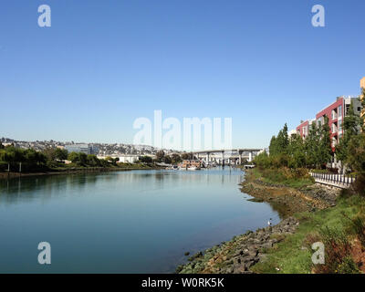 Shoreline of Mission Creek lined with buildings, house boats and highway going over creek in the distance in San Francisco, California. - Stock Photo