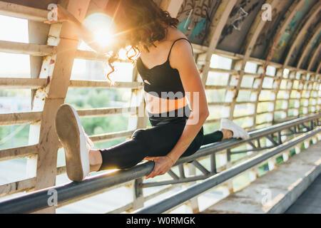 Slender young brunette woman street dancer gymnast sits in splits pose on street bridge at the sunrise - Stock Photo