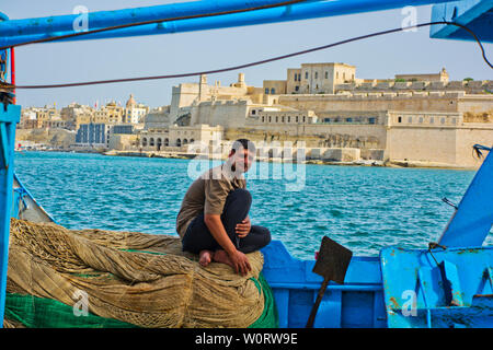 Fisherman sitting on fishing nets with view across the Grand Harbour in Valletta, Malta - Stock Photo