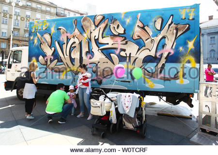 ZAGREB, CROATIA - MAY 19, 2018 : People with children standing in front of a truck painted with graffiti on Jelacic square in Zagreb, Croatia. - Stock Photo