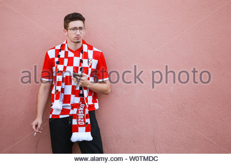 ZAGREB, CROATIA - JULY 15, 2018 : Croatian football fan standing next to the red wall on Ban Jelacic Square in Zagreb, Croatia. - Stock Photo