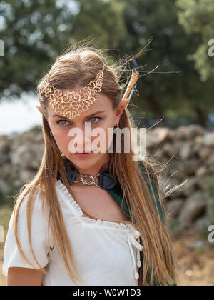 Blonde girl with blue eyes and makeup with elf ears poses in the field with a bow and a green cape. - Stock Photo