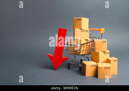 Shopping cart supermarket with boxes and a red arrow down. Falling consumer demand, declining exports or imports. The decline in production of goods a - Stock Photo