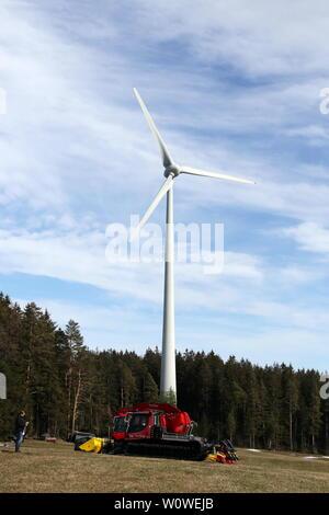 Windrad und Pistenbully auf einer grünbraunen Wiese im Wittenbach beim Weltcup der Nordische Kombination Schwarzwaldpokal 2019 in Schonach - Stock Photo