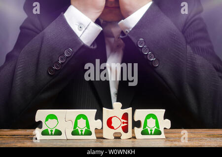 Businessman sitting in despair over the not assembled puzzles symbolizing a team of employees. Toxic or incompetent worker who fails to comply tasks a - Stock Photo